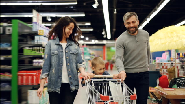 Slow motion of happy family father, mother and child running through supermarket with shopping cart, smiling and laughing. Having fun in shop and people concept. Slow motion of happy young family father, mother and child running through supermarket with shopping cart, smiling and laughing. Having fun in shop and people concept. woman pushing cart stock videos & royalty-free footage