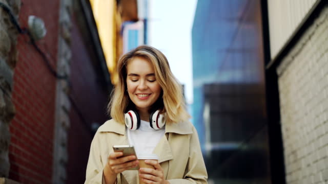 vídeos de stock e filmes b-roll de slow motion of happy girl using smartphone while walking in the street wearing coat and holding take-away coffee. urban lifestyle, millennials and young people concept. - mensagem sms