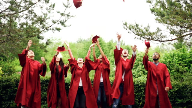 slow motion of happy graduates throwing mortarboards in air, laughing and celebrating graduation on college campus. education, success and modern youth concept. - tocco accademico video stock e b–roll