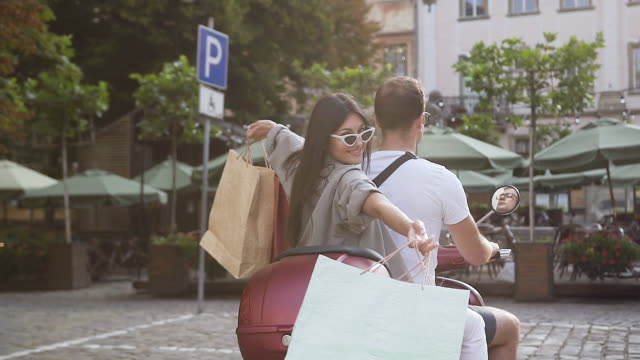 Slow motion of happy smiling young woman with shop packages in her hands riding on scooter with her male friend on the urban street