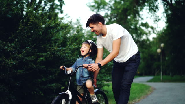 Slow motion of happy young man loving father teaching his child to cycle in green park in summer, little boy is laughing, shouting and enjoying weekend with dad.