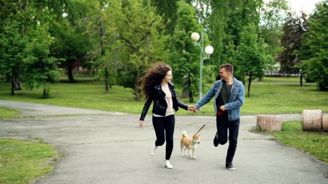 slow motion av glada ungdomar som kör parken med glad hund njuter av natur med vackra sommarstaden landskap i bakgrunden. - gå tillsammans bildbanksvideor och videomaterial från bakom kulisserna