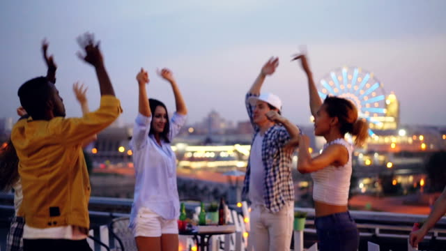 vídeos de stock e filmes b-roll de slow motion of happy youth dancing at open-air party raising hands and relaxing while dj is mixing music. beautiful city with evening lights is visible in background. - descuidado