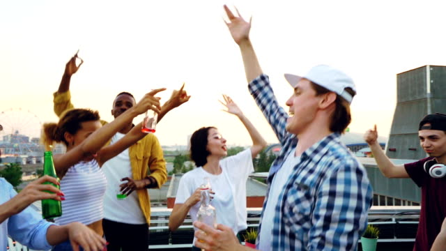 vídeos de stock e filmes b-roll de slow motion of happy youth dancing at outdoor party on roof having fun and relaxing at weekend holding bottles. modern lifestyle, beverage and partying concept. - descuidado