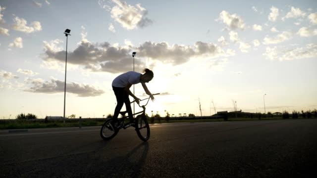 slow motion of hipster young man losing control of bike failing jump trick - niedoskonałość filmów i materiałów b-roll