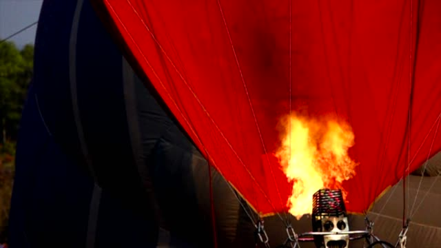 Slow motion of Hot air balloon. Burner directing flame into envelope on background helium blimp high in sky video