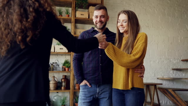 vídeos de stock e filmes b-roll de slow motion of housing agent giving keys to buyers of new apartment, happy husband and wife are hugging and kissing, man is shaking hands with female realtor. - chave