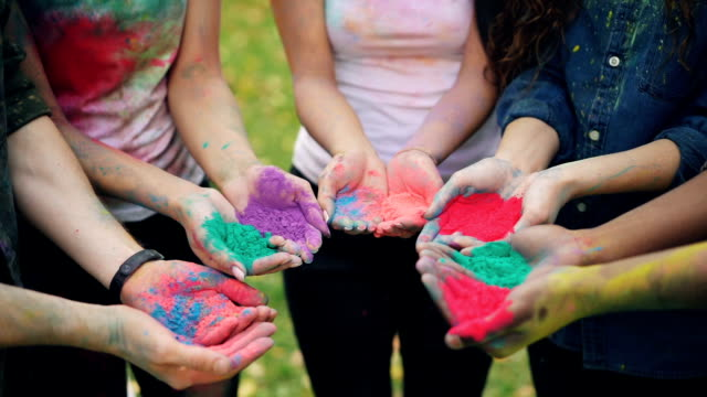 vídeos de stock e filmes b-roll de slow motion of human hands holding multicolor powder paint gulal for holi festival ceremony standing outside on lawn. people, fun and celebration concept. - holi