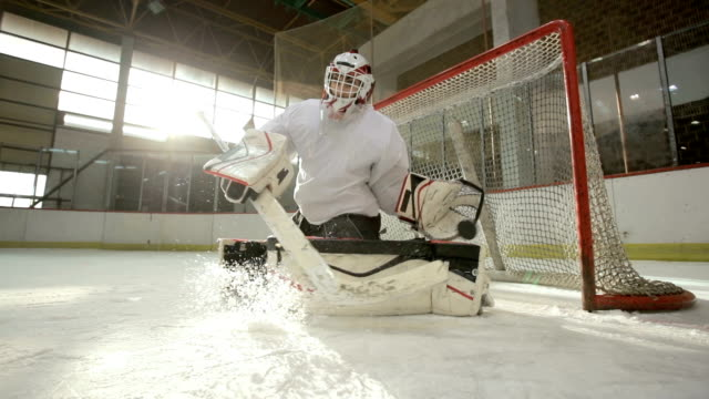 Slow motion of ice hockey goalie blocking the shot and defending his goal in ice hockey rink. video