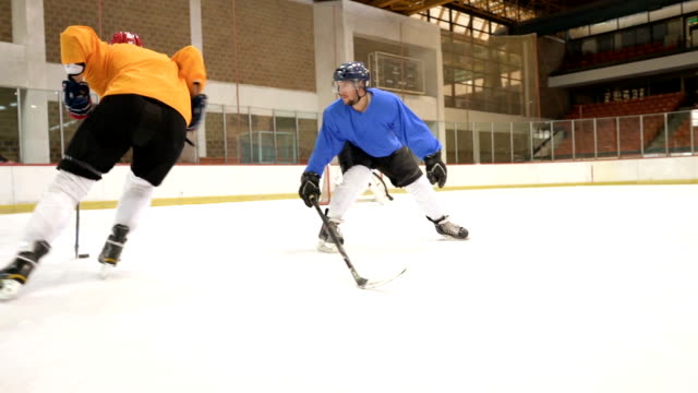 slow motion of ice hockey players in action on a sports match in ice hockey rink. - hockey stock videos and b-roll footage