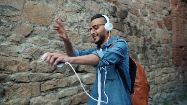 Slow motion of joyful African American guy listening to music in headphones Slow motion of joyful African American guy listening to music in headphones outdoors holding smartphone walking and dancing in the street. People and happiness concept. headphones stock videos & royalty-free footage