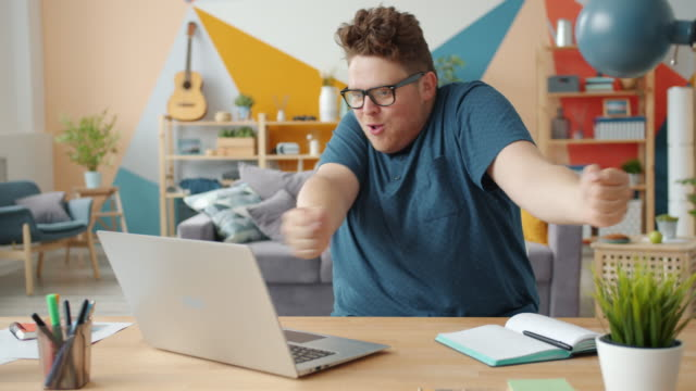 Slow motion of joyful businessman celebrating success at work using laptop at home video