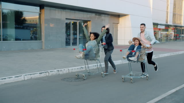 Slow motion of joyful young people friends riding shopping carts outdoors Slow motion of joyful young people friends riding shopping carts outdoors, men are pushing trolleys with women. Happiness and entertainment concept. woman pushing cart stock videos & royalty-free footage