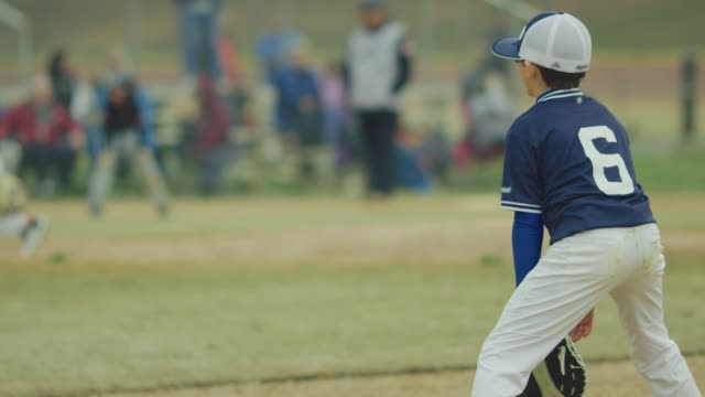 Slow motion of kid catching ball on the field during a baseball game video