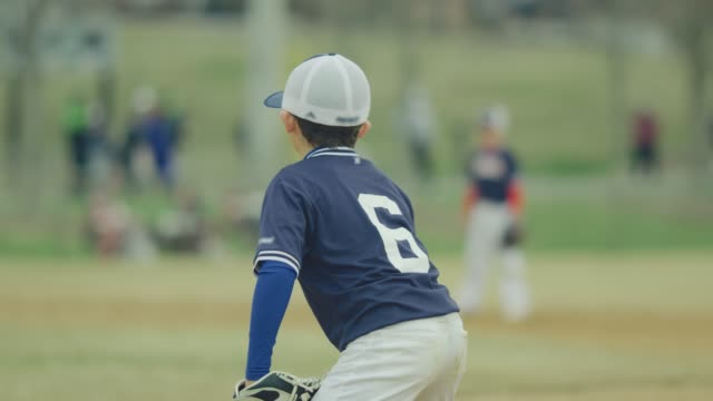Slow motion of kid in position in middle of baseball game video