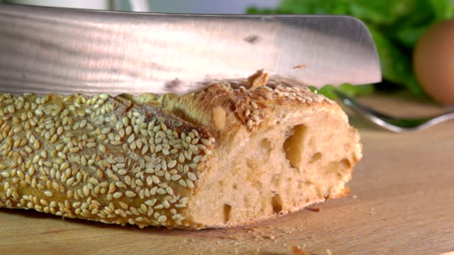 Slow motion of knife cutting baguette with sesame seeds Slow motion of crumbs fly from the knife cutting baguette with sesame seeds cooking utensil stock videos & royalty-free footage