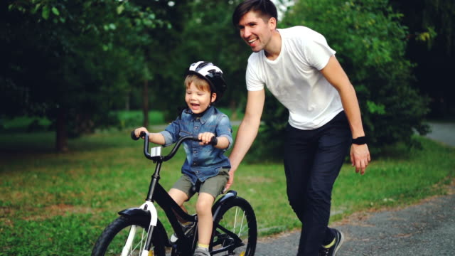 Slow motion of laughing child cycling in park with careful father who is teaching him to ride bicycle. Happy young family, fatherhood and childhood, active lifestyle concept.