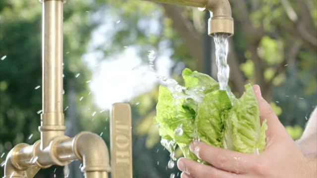 Slow motion of lettuce washed in water in an outdoor kitchen video