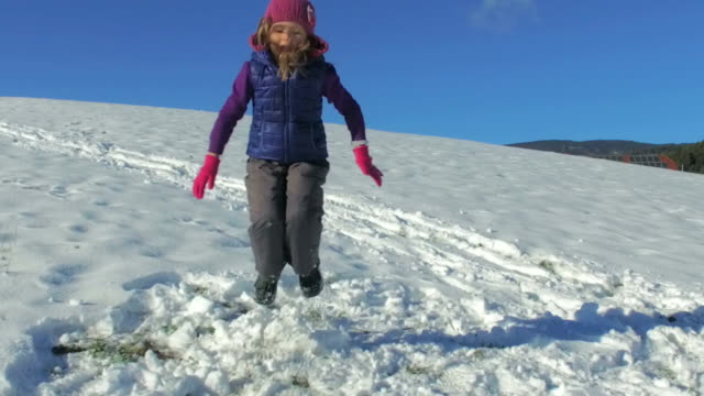Slow motion of little girl jumping in the snow video