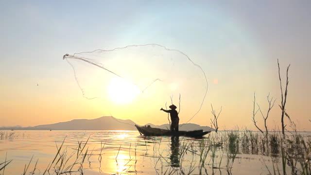 slow motion of local lifestyles of fisherman at lagoon sunset - łowić ryby filmów i materiałów b-roll