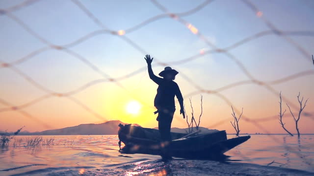 slow motion of local lifestyles of fisherman at lagoon sunset - fishing stock videos and b-roll footage
