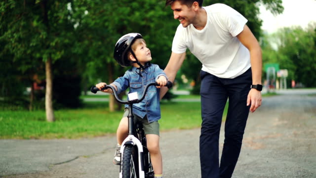 Slow motion of loving dad teaching his adorable son to ride bicycle in park holding bike and talking to child. Fatherhood, childhood and active lifestyle concept.