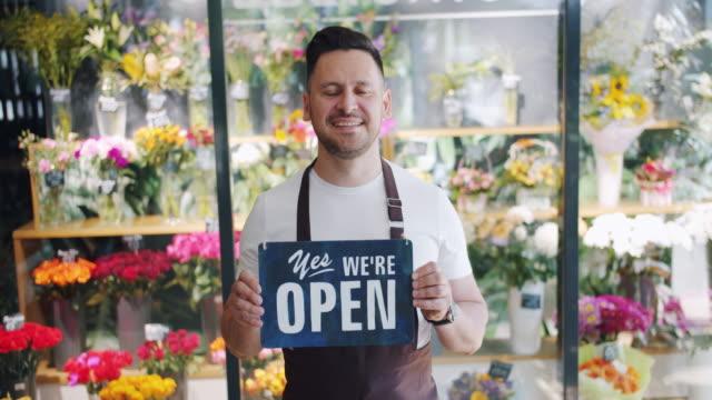 vídeos de stock, filmes e b-roll de o movimento lento da terra arrendada masculina do florista nós é ardósia aberta que está na loja da flor - aberto