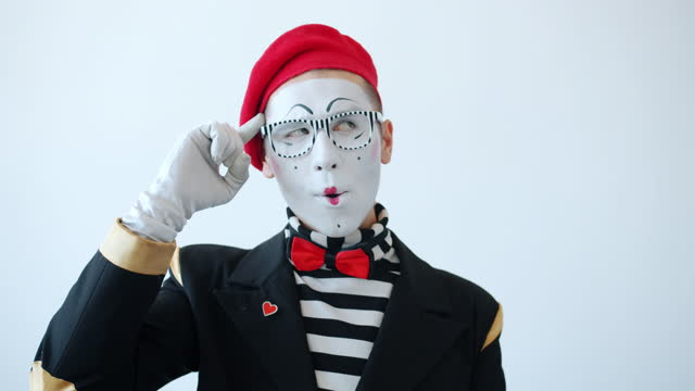 Slow motion of male mime showing crazy hand gesture twisting finger at temple Slow motion of male mime showing crazy hand gesture twisting finger at temple and looking at camera on white background. Body language and people concept. gesturing stock videos & royalty-free footage