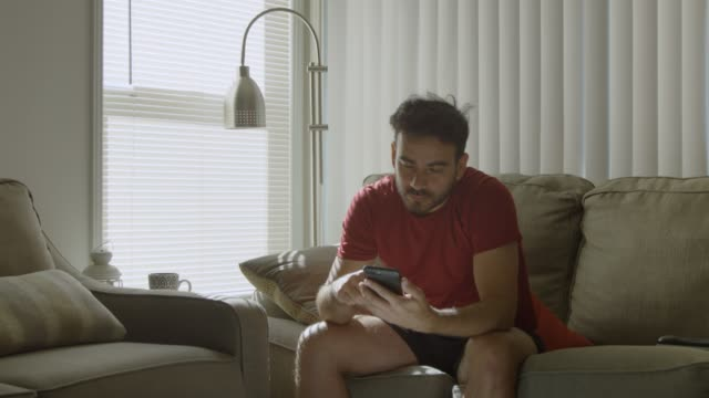 Slow motion of man at home scrolling on cell phone and looking bored video