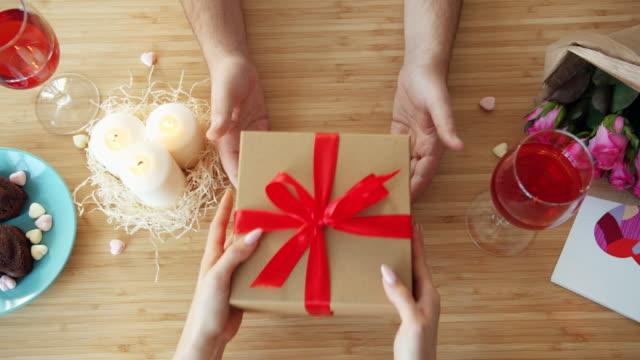 slow motion av man ger närvarande i en presentförpackning till kvinna i kaféet under middagen - wine box bildbanksvideor och videomaterial från bakom kulisserna
