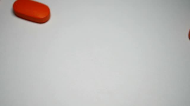 vídeos de stock, filmes e b-roll de câmera lenta de homem derramando comprimidos em papel branco - punhado