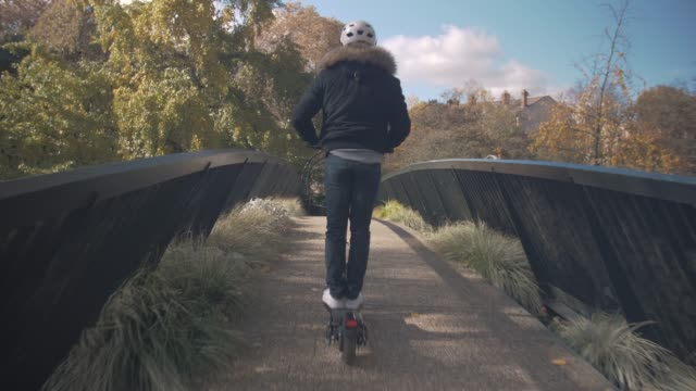 slow motion of man with helmet using electric scooter on a bridge - monopattino elettrico video stock e b–roll
