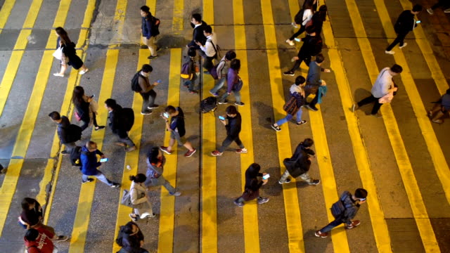 Slow motion of many people using smart phone while walking the zebra crossing road Slow motion of many people using smart phone while walking the zebra crossing road in Hong Kong at Night yellow stock videos & royalty-free footage