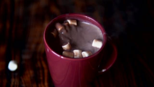 vídeos de stock, filmes e b-roll de movimento lento do marshmallow que cai no copo com bebida quente do cacau do chocolate - chocolate quente