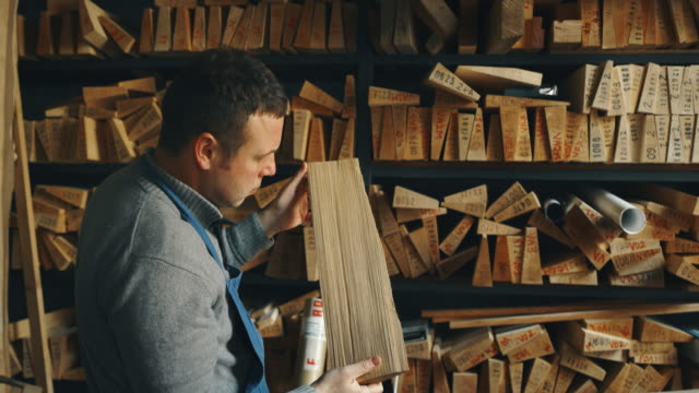 Slow motion of master artisan luthier choosing a wood for creation of handmade violin  in a workshop