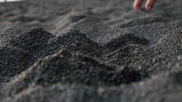 vídeos y material grabado en eventos de stock de el movimiento lento de las manos de los hombres toma la arena volcánica negra, vertiendo a través de los dedos en reynisfjara black sand beach. - basalto