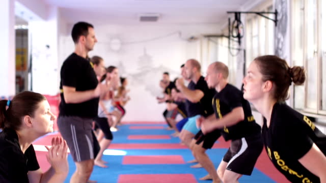 Slow motion of mix group of people exercising A Large group of people exercising in a gym. they are jumping and doing durability test durability stock videos & royalty-free footage