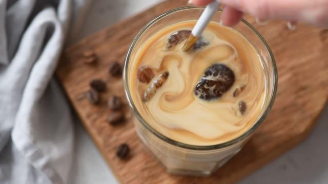 langsame bewegung der mischung von eis kaffee mit sahne - milchkaffee stock-videos und b-roll-filmmaterial