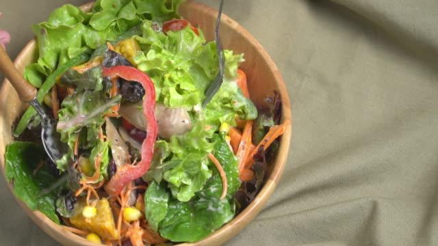 vídeos de stock e filmes b-roll de slow motion of mixing salad bowl. - saladeira