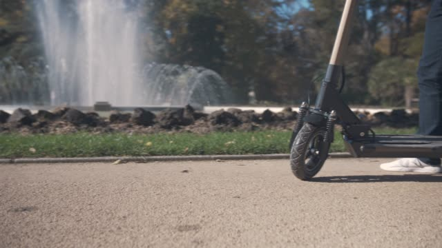slow motion of modern man starting on electric scooter in park with fountain - monopattino elettrico video stock e b–roll
