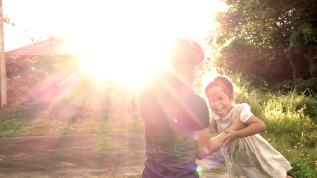 Slow motion of mother and daughter spinning around in flare sunset video