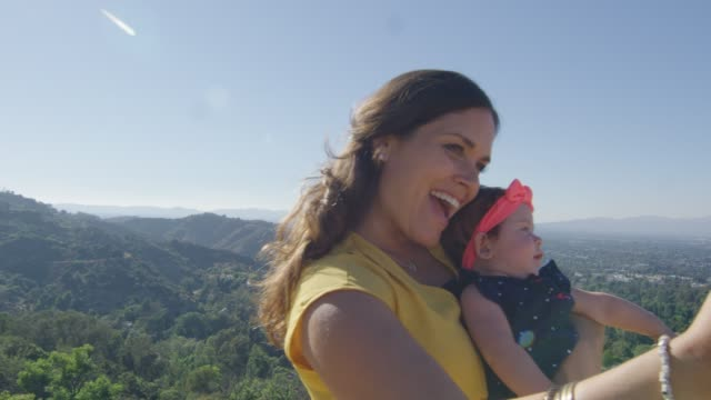 Slow motion of mother taking selfie with baby by mountains video
