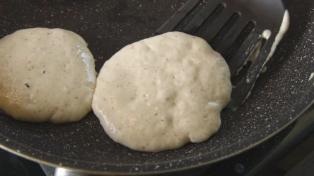 Slow motion of pancakes being cooked and turned on a pan video