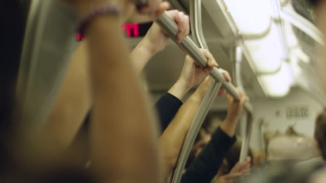 Slow motion of people's hands holding onto railings inside a moving train