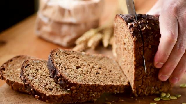 stockvideo's en b-roll-footage met slow motion van persoon snijden roggebrood - brood
