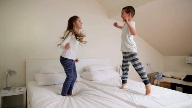 Slow motion of playful children jumping on the bed and having fun.