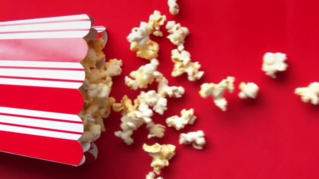 vídeos de stock, filmes e b-roll de câmera lenta de pop corn caindo em um fundo vermelho a 120 fps - balde pipoca