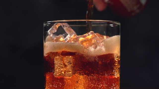 Slow motion of pouring cola soda drink to glass with ice cubes, macro close up video