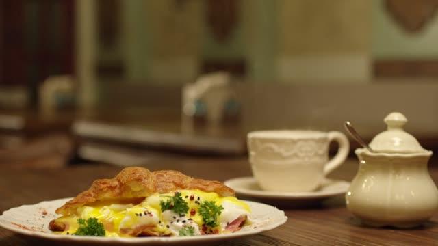 Zeitlupe des Gießens von Eiersaft aus Croissant in den Teller. Profi-Koch schneiden Croissant Omelett durch Gabel. Frühstücksartikel auf dem Tisch im Restaurant . Aufnahme auf RED EPIC Kamera . – Video
