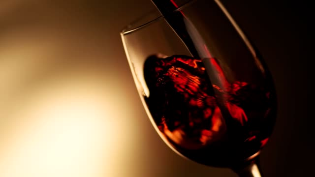 zeitlupe des gießens von rotwein aus der flasche in den kelbesen mit kopierraum links. - cabernet sauvignon traube stock-videos und b-roll-filmmaterial